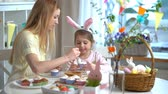 icing : Young mother and her cute little daughter wearing funny rabbit ears are cooking Easter cupcakes sitting at a festive table with basket, eggs and Bunny. Slow Motion