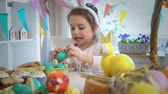 zajączek wielkanocny : Little girl eating Chocolate Easter Eggs sitting at the holiday table with a basket and a yellow rabbit. Slow Motion