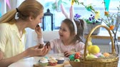 zajączek wielkanocny : Mother And Daughter eating Chocolate Easter Eggs sitting at the holiday table with a basket and a yellow rabbit. Slow Motion
