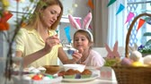 zajączek wielkanocny : Young mother and her cute little daughter wearing funny rabbit ears are cooking Easter cupcakes sitting at a festive table with basket, eggs and Bunny Wideo