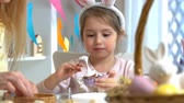 zajączek wielkanocny : Young mother and her cute little daughter wearing funny rabbit ears are cooking Easter cupcakes sitting at a festive table with basket, eggs and Bunny. Slow Motion