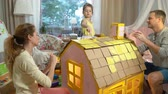 ипотека : Young family with little girl building and painting toy cardboard house together. Стоковые видеозаписи
