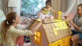 sahip : Young family with little girl building and painting toy cardboard house together. Slow motion- Stok Video