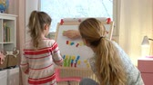 азбука : Early childhood development. Little girl are learning to write letters with special desk. Young woman teaching her child the alphabet. Play and learn