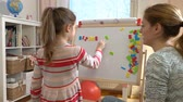 oktatói : Early childhood development. Young mother explaining arithmetic to cute little daughter with special desk at home. Play and learn. Slow motion