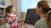 iskolai tábla : Early childhood development. Young mother explaining arithmetic to cute little daughter with blackboard at home. Play and learn. Slow motion