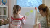 образовательный : Little daughter and her mother are drawing with colorful pencils. Young mom and her daughter are playing and learning. Slow motion