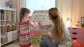азбука : Early childhood development. Little girl are learning to write letters with special desk. Young woman teaching her child the alphabet. Slow motion