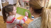 iskoláslány : Early childhood development. Little girl learning time with clock toy at home. Play and learn. Slow motion