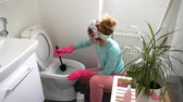 sedes : Woman with a rubber glove cleans a toilet bowl using means for cleaning