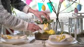 sofra takımı : Young woman is setting easter festive table with bunny and eggs decoration Stok Video