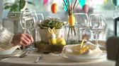 decorative rabbit : Young woman is setting easter festive table with bunny and eggs decoration Stock Footage