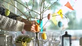 sofra takımı : Young woman is setting easter festive table with bunny and eggs decoration. Slow Motion