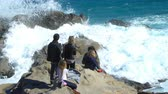 İtalya : Family enjoy the sun and waves on the coastal cliffs on azure coast. Ligurian Sea Bay Stok Video