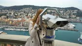 gözcü : Traveler woman watching through the stationary binoculars at a scenic overlook in Nice, France Stok Video