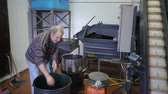 smród : Production of perfume essences using steam in a distillation cube in a small alpine village. An elderly man puts rosemary leaves and flowers in the distillation apparatus. Real people. Wideo