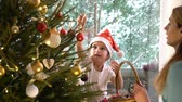 pomocník : Little cute girl in a red hat with her mom decorate the Christmas tree