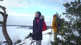 montanhismo : Couple on winter hike in mountains, backpackers walking on snow in Scandinavia. Slow motion