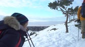 bengala : Group of young people hiking in mountains in winter. Backpackers walking on snow in Scandinavia, help each other, take pictures and enjoy nature. Slow motion