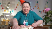 longevity : Happy senior woman holding cake to web camera while celebrating birthday with her family via video chat Stock Footage