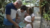 nagyapa : KRISTIANSAND, NORWAY - JULY 07, 2018: Mature couple with two granddaughters carefully watch the map of the amusement zoo Park Stock mozgókép