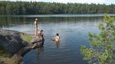 優しい : Family swimming in a forest lake in Finland. Finland is one of the most environmentally friendly countries in the world with the cleanest waters.