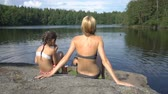 優しい : A young mother with her little daughter is sunning on the rocky shore of a forest lake in Finland. Finland is one of the most environmentally friendly countries in the world with the cleanest waters.