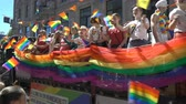 hoşgörü : OSLO, NORWAY - JUNE 30, 2018: A lot of fancy-dress people with rainbow flags dance, sing and laugh in the street. The Pride Parade, the highlight of Oslo Pride Week, is a huge, vibrant parade filling the city streets. Stok Video