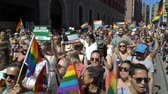 homosexual : OSLO, NORWAY - JUNE 30, 2018: A lot of fancy-dress people with rainbow flags dance, sing and laugh in the street. The Pride Parade, the highlight of Oslo Pride Week, is a huge, vibrant parade filling the city streets. Stock Footage