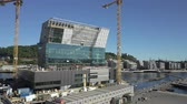 oslo : OSLO, NORWAY - JUNE 30, 2018: Construction of a new modern elite residential areas. Building site with cranes and containers in Bjorvika in Oslo, next to the Opera House.