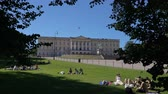 monarşi : OSLO, NORWAY - JUNE 30, 2018: Young people on the grass in the park in front of the royal palace Stok Video