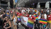 homo : OSLO, NORWAY - JUNE 30, 2018: A lot of fancy-dress people with rainbow flags dance, sing and laugh in the street. The Pride Parade, the highlight of Oslo Pride Week, is a huge, vibrant parade filling the city streets. Slow motion Stock Footage