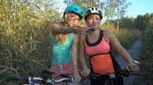 cana : Two young women use GPS Navigation At Smartphone On Bicycle while Cycling in nature