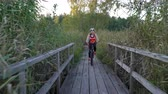 canne : Two young women ride bicycles on a wooden ecological trail among the reeds