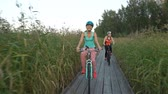 cana : Two young women ride bicycles on a wooden ecological trail among the reeds