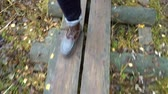 болото : A man walking along an ecological natural educational trail through the northern autumn forest in a nature park in Finland. Close-up of feet in boots slow motion Стоковые видеозаписи