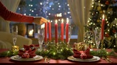 lentejoula : Fale hand lights christmas candles. Festival red table setting with garland and Christmas tree in the background Slow motion