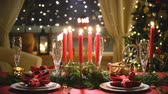 lentejoula : Festive christmas red table setting with candles, garland and Christmas tree in the background