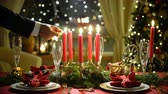 Male hand lights christmas candles. Festival red table setting with garland and Christmas tree in the background Stock Footage