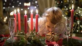 christmas fragrances : Cute little girl with Christmas cookies. Festival red table setting with candles, garland and Christmas tree in the background. Slow motion
