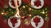 Female hand lights christmas candles. Festive red table setting with garland. Top view