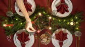 lentejoula : Female hand lights christmas candles. Festive red table setting with garland. Top view
