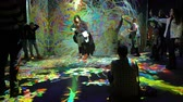 moving image : HELSINKI, FINLAND - JAN 06, 2019: Massless Exhibition - immersive interactive graphic digital installations by a group of Japanese artists TeamLab at the Amos Rex Museum. Visitors enjoy the new modern digital art