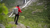 prozkoumat : Caucasian Backpacker Enjoying Scenic Waterfall Vista in the Norway.