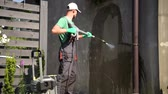 podložka : Pressure Washer Cleaning Dirty House Elevation. Caucasian Cleaning Specialist