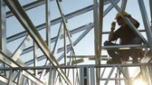рамка : Contractor Worker with Walkie Talkie in Hand on the Steel Frame of the House