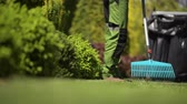 préau : Professional Gardener Raking Grass in a Backyard Garden. Garden Maintenance