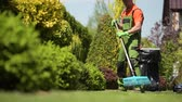 préau : Worker Raking Grass Field in a Garden. Caucasian Gardener in His 30s. Vidéos Libres De Droits