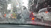sıkışmış : viewing from in car behind windshield during heavy traffic raining and motor biker wearing rain suit passing Stok Video