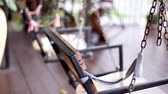 inscrutable : An empty wooden swing rocks back and forth on a wooden terrace in the garden